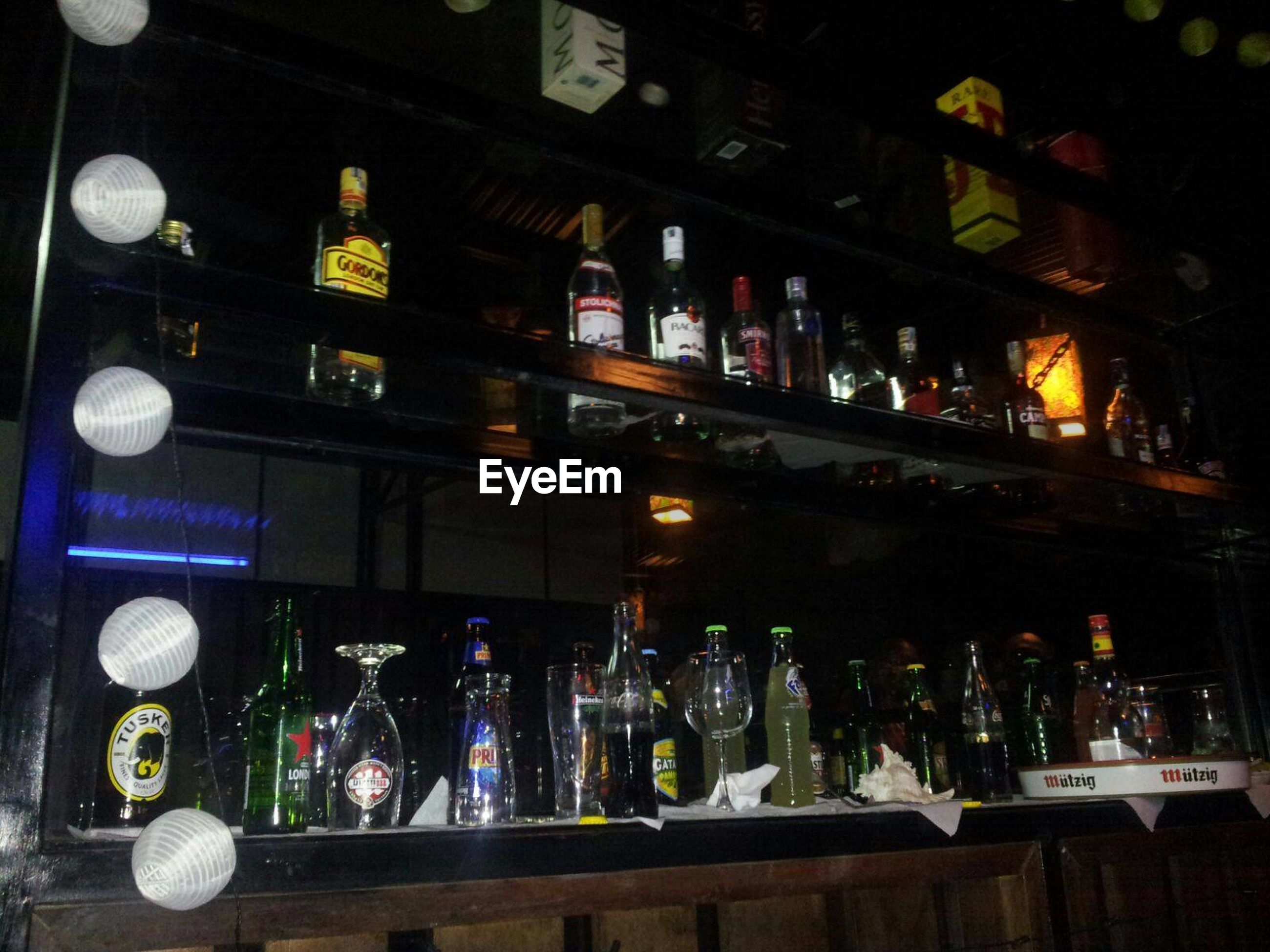 variation, choice, large group of objects, illuminated, arrangement, collection, retail, night, abundance, display, order, repetition, shelf, group of objects, bar - drink establishment, multi colored, buying, person