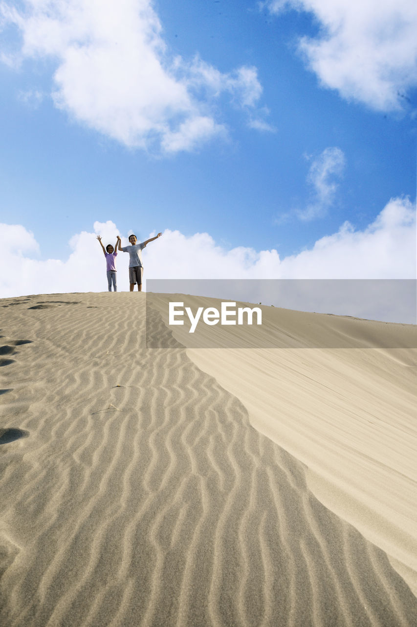 Low Angle View Of Siblings Standing On Sand Dune Against Sky