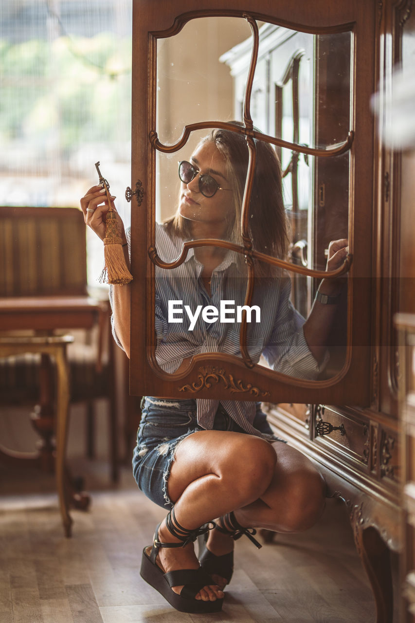 Young Woman Seen Through Cabinet Glass Door At Home
