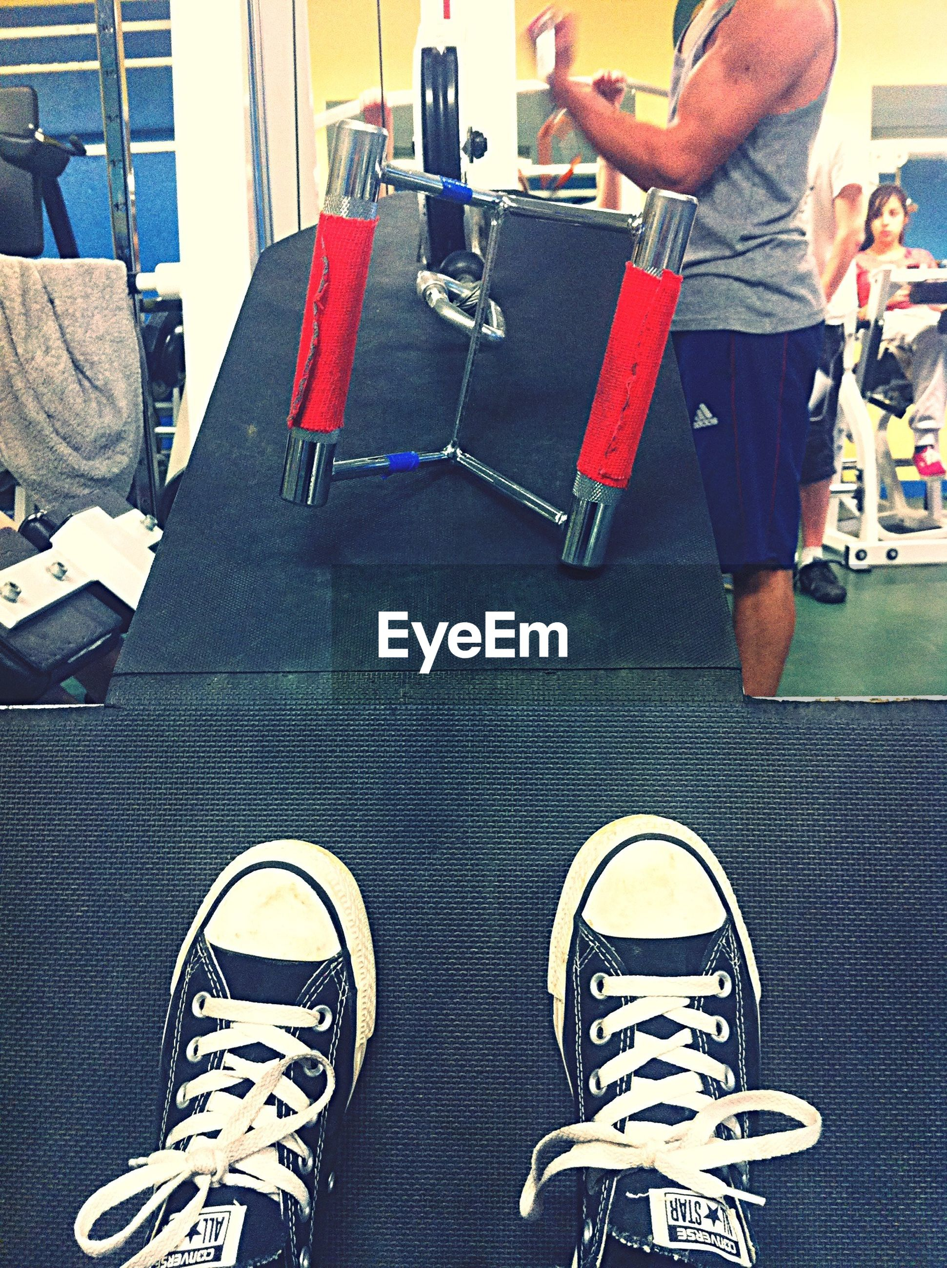 low section, shoe, person, personal perspective, men, lifestyles, human foot, high angle view, indoors, standing, footwear, leisure activity, canvas shoe, jeans, red, part of, unrecognizable person