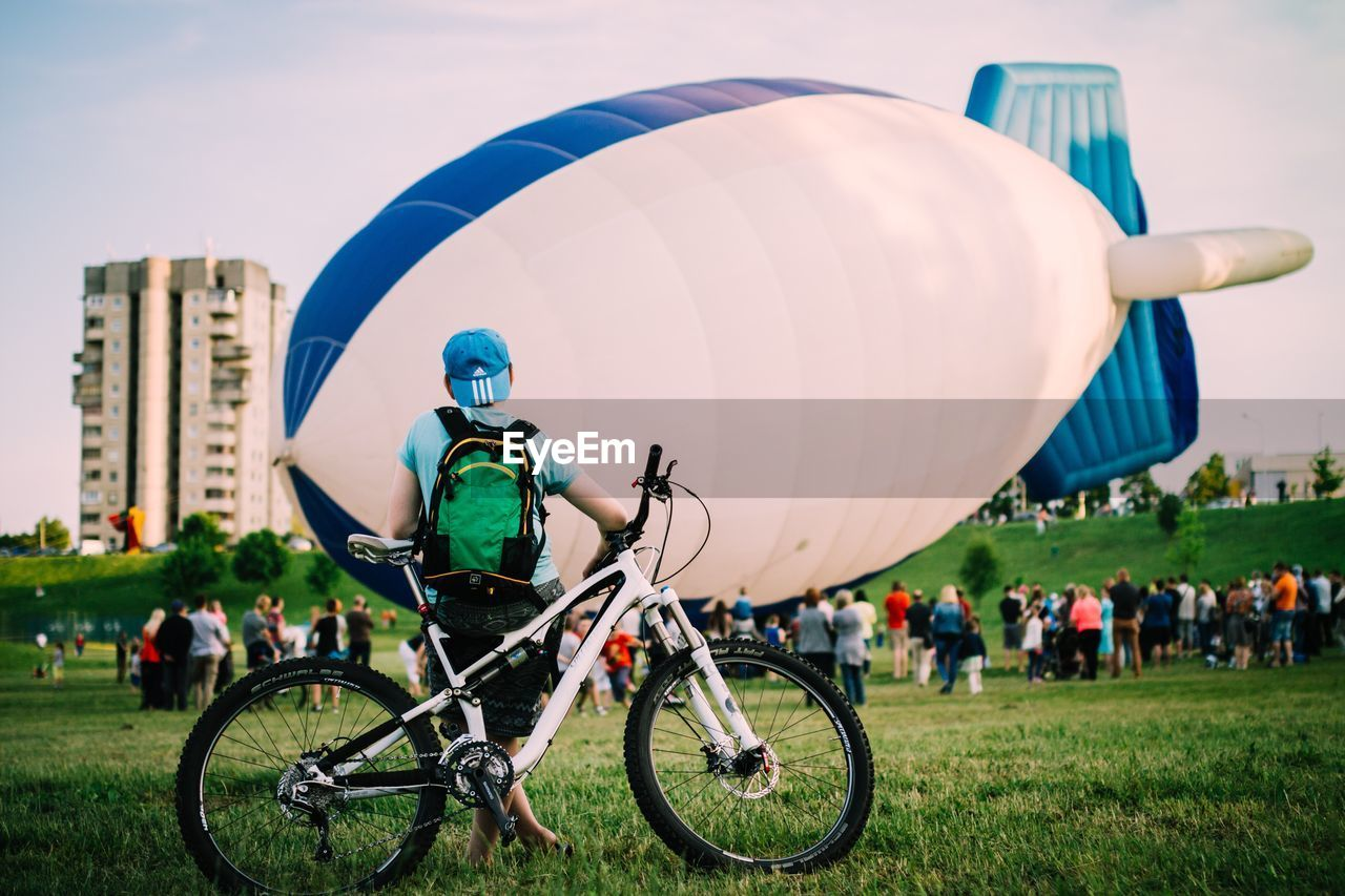 grass, real people, outdoors, leisure activity, sport, large group of people, bicycle, field, day, adventure, lifestyles, men, sky, nature, playing field, building exterior, full length, tree, people