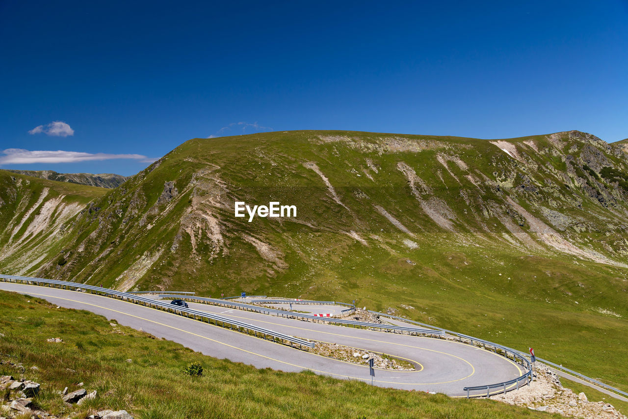 High Angle View Of Road By Mountain Against Blue Sky
