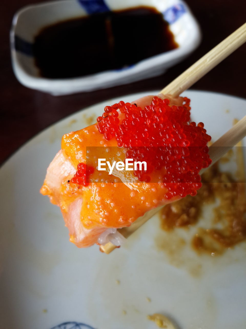 High angle view of sushi roll with chopsticks over plate