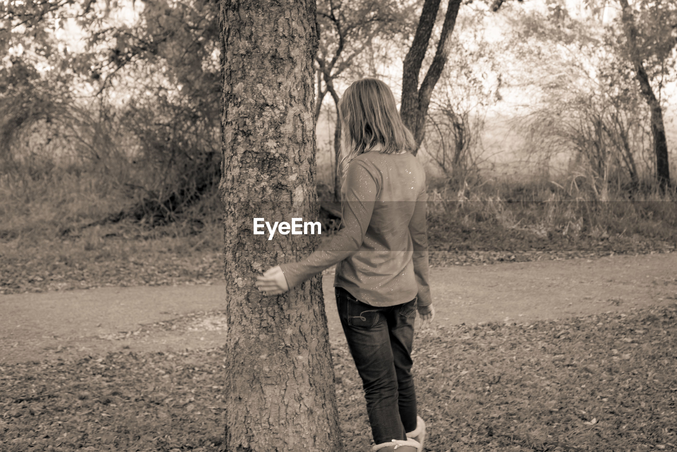 REAR VIEW OF WOMAN STANDING ON TREE TRUNK