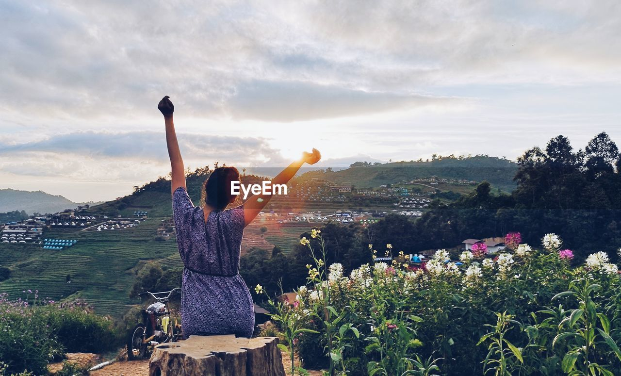 Rear view of women with flowers on mountain against sky