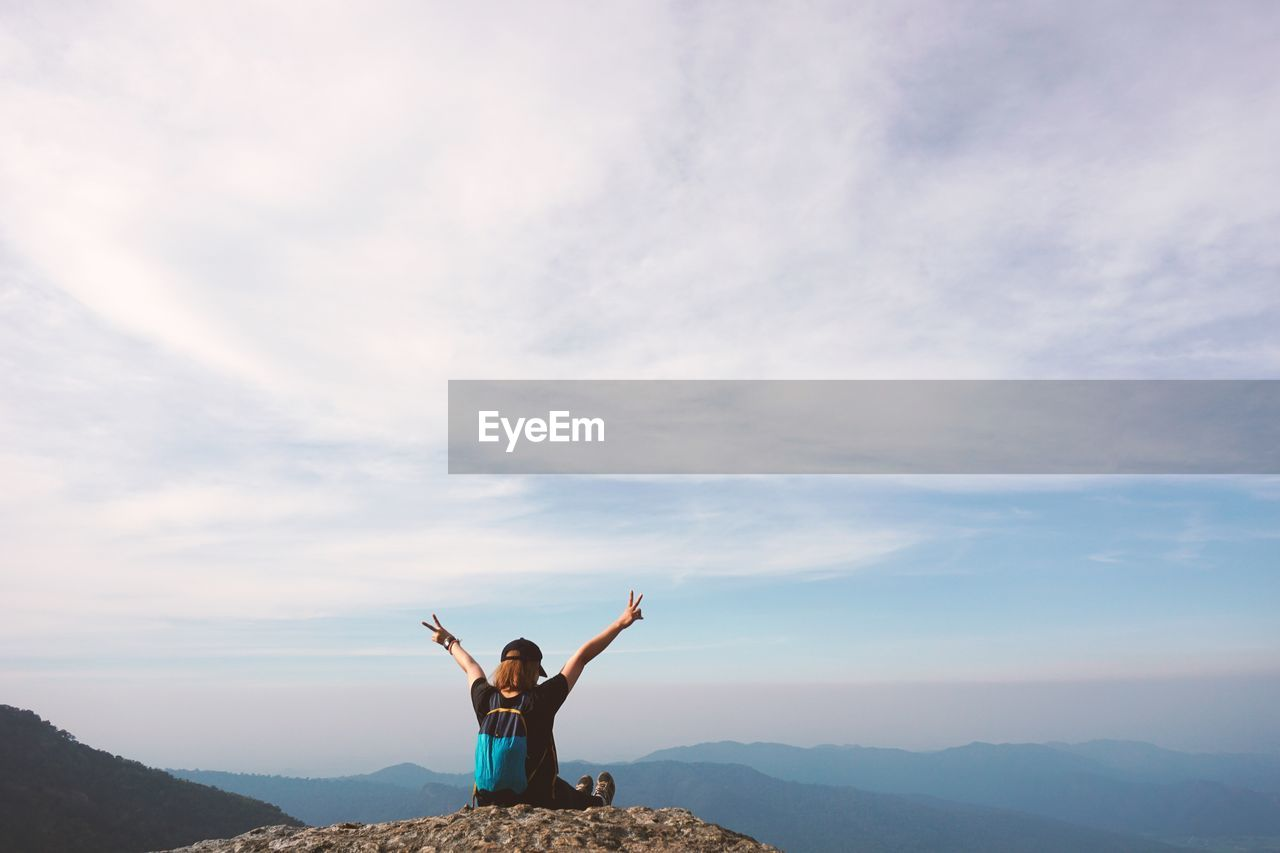 Woman Gesturing Peace Sign While Sitting On Mountain Against Sky