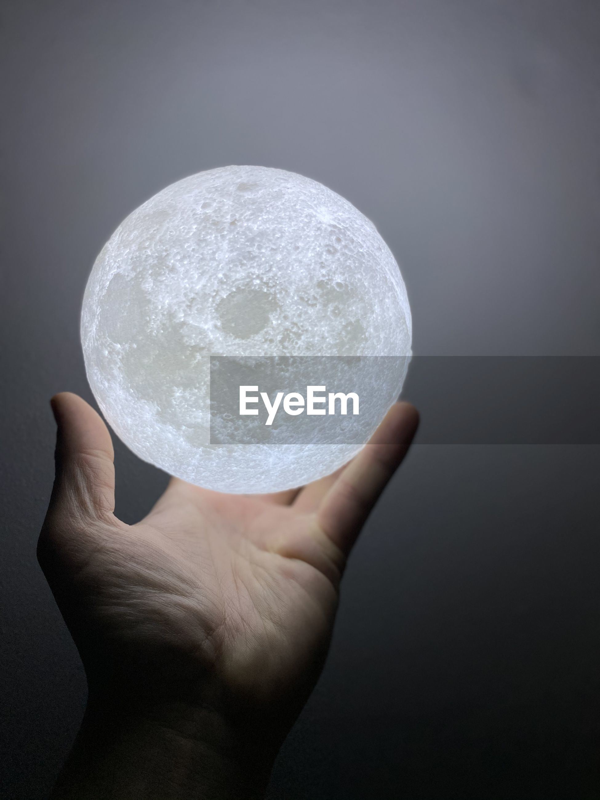 Digital composite image of man holding full moon against gray background
