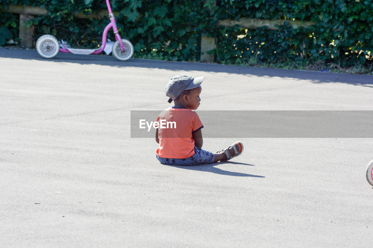 Boy Wearing Cap While Sitting On Road During Sunny Day