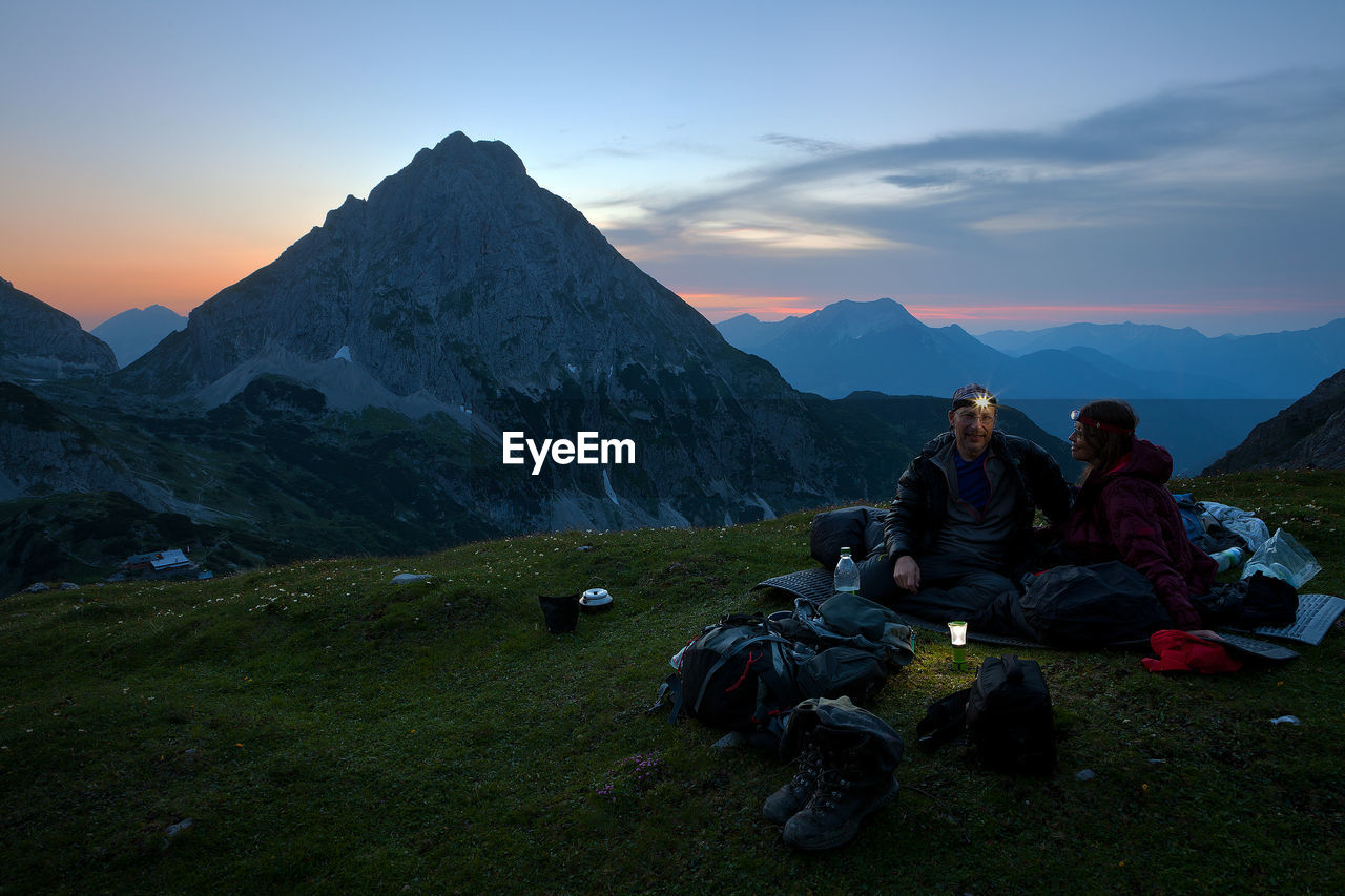 Smiling Mature Couple Camping On Top Of Mountain At Dusk