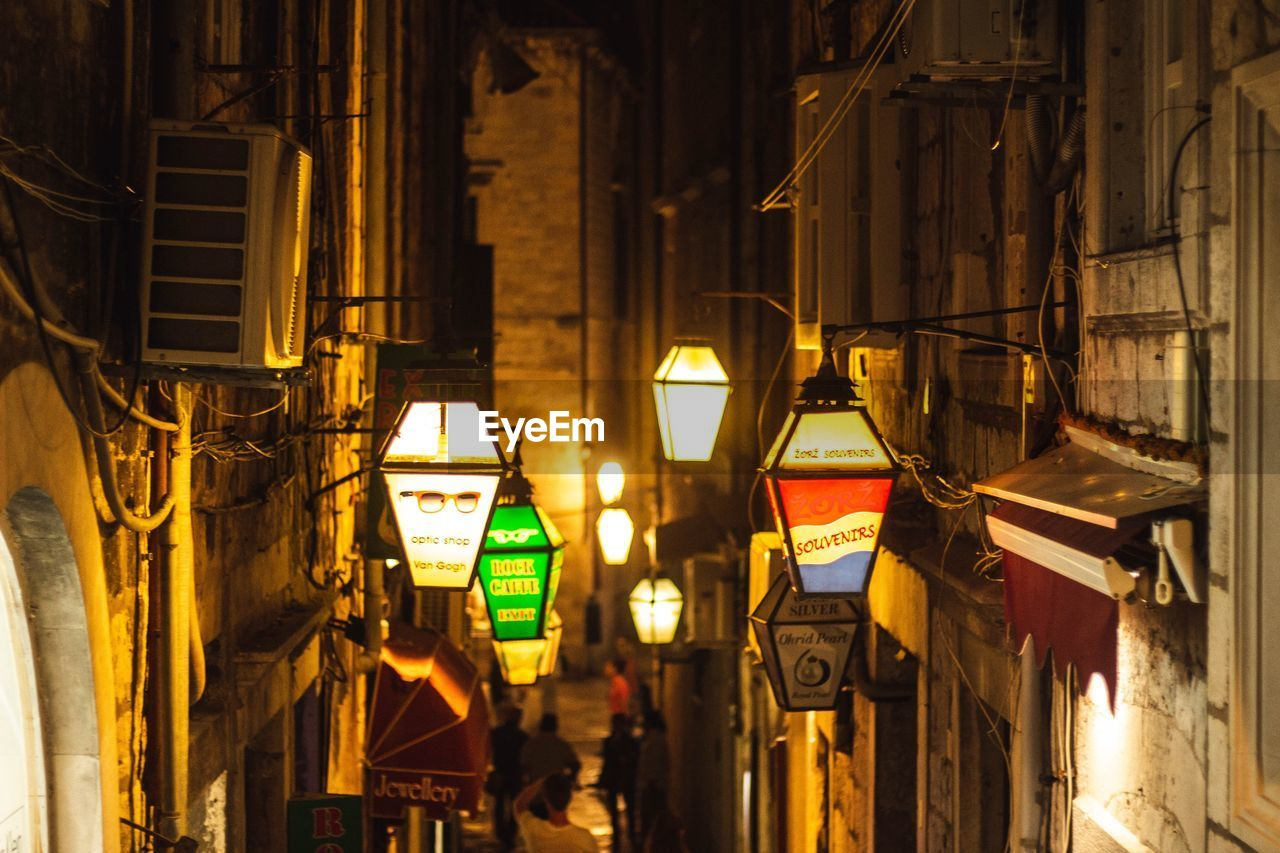 illuminated, night, lighting equipment, building exterior, architecture, built structure, no people, city, building, glowing, residential district, light, hanging, electric light, outdoors, street, lantern, wall - building feature, light - natural phenomenon, focus on foreground, electric lamp, alley