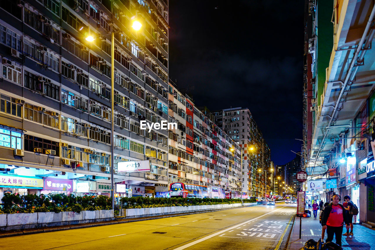 night, illuminated, architecture, building exterior, city, built structure, street, transportation, road, building, city life, outdoors, glowing, sky, real people, sign, street light, city street, group of people, lighting equipment