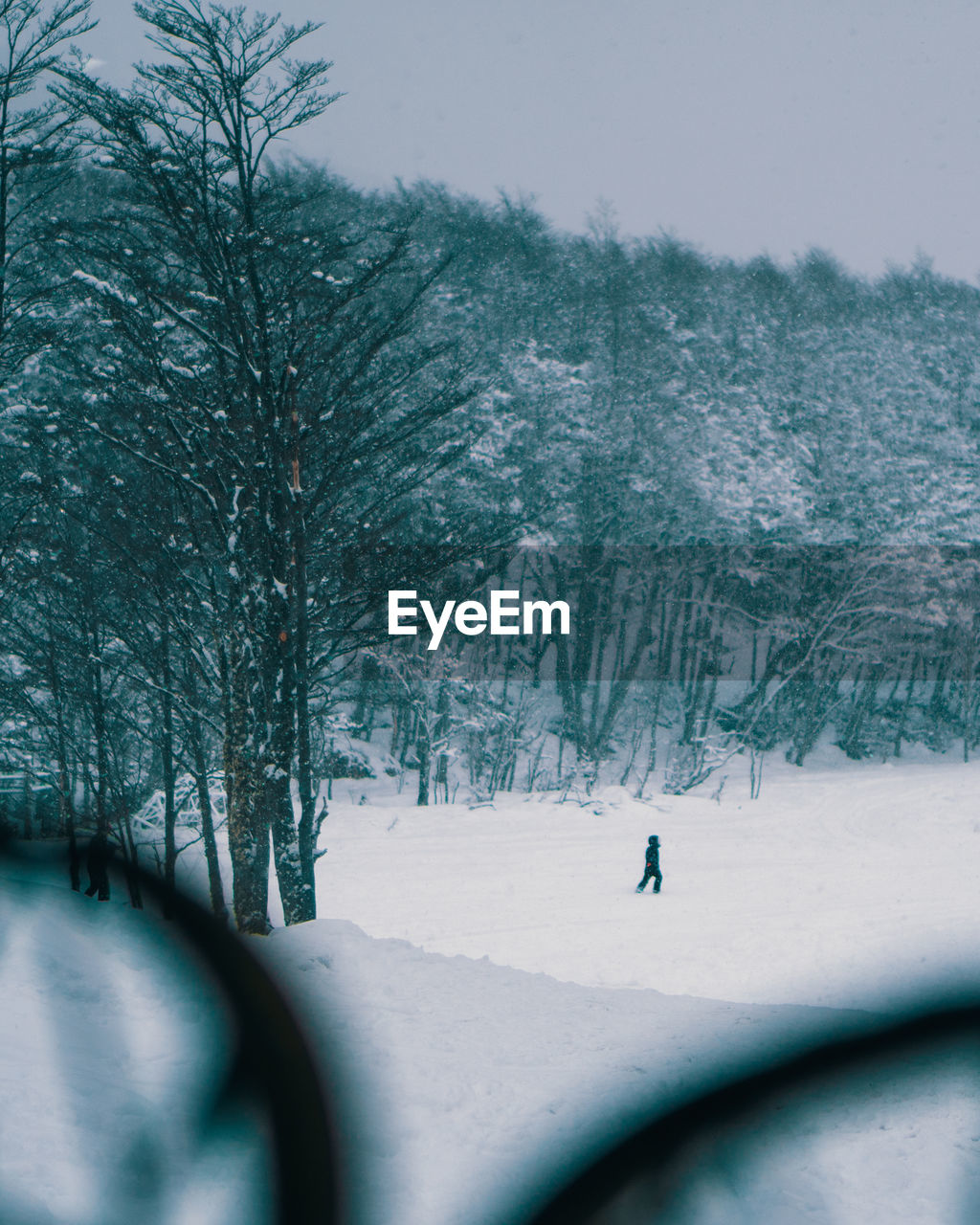 Distant view of person walking on snowy landscape