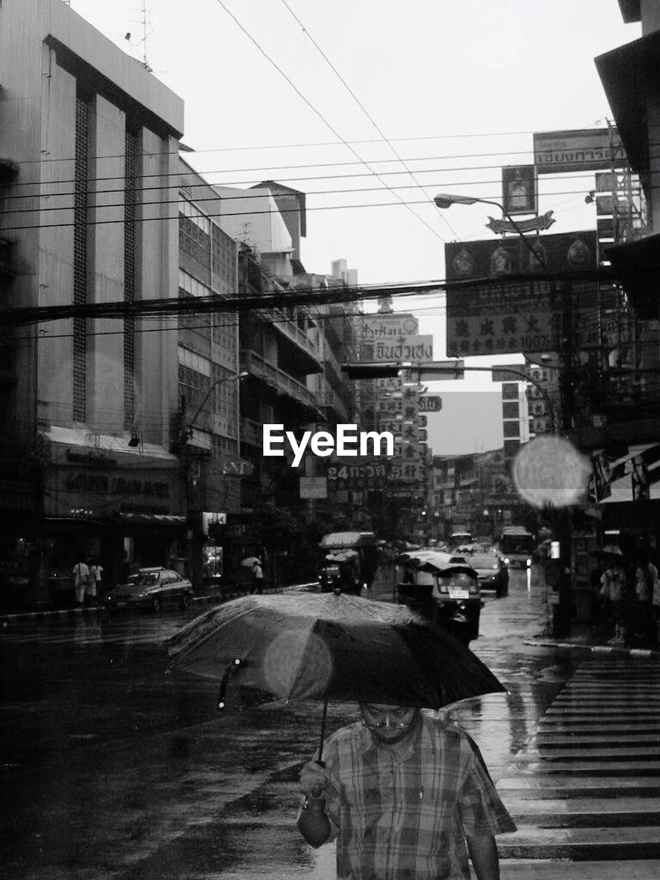 rain, street, city, architecture, built structure, wet, rainy season, building exterior, city life, rear view, road, outdoors, real people, day, one person, sky, people, adult