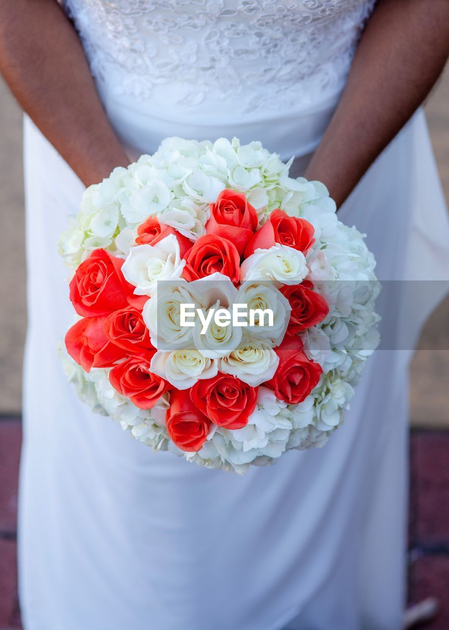 midsection, women, real people, one person, adult, flower, rose, bouquet, rose - flower, wedding, flowering plant, wedding dress, celebration, flower arrangement, lifestyles, white color, event, newlywed, bride, standing, hand, wedding ceremony