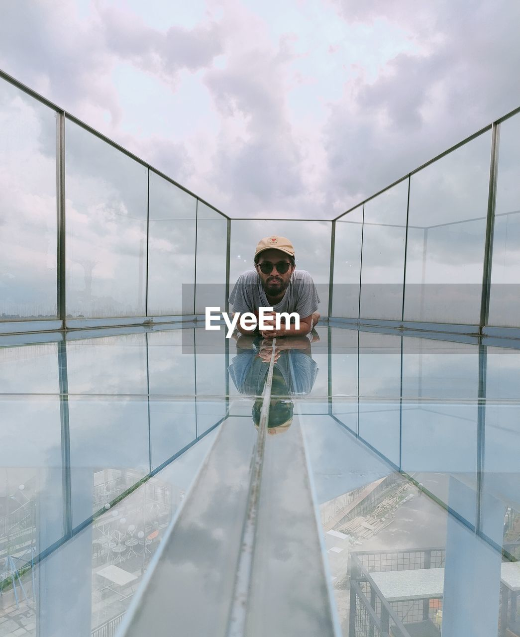 Man standing on glass against sky