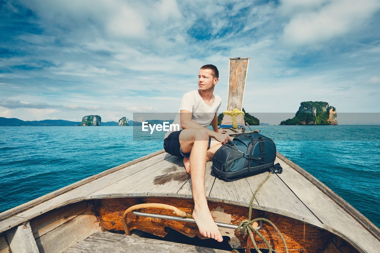 Man Traveling On Longtail Boat At Sea Against Cloudy Sky