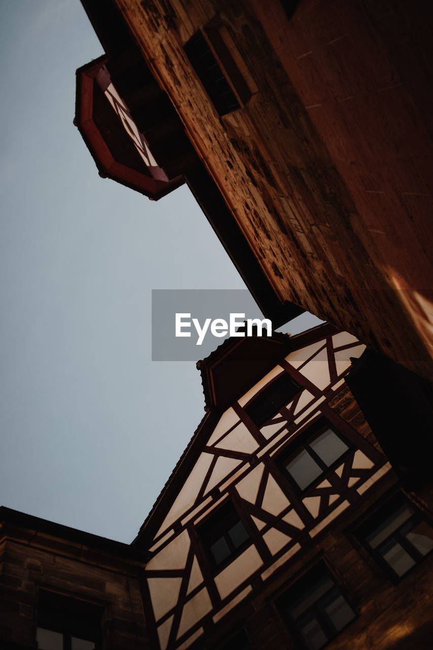 low angle view, architecture, built structure, building exterior, building, sky, no people, window, nature, outdoors, lighting equipment, roof, day, house, residential district, wood - material, dusk, clear sky, glass - material, ceiling