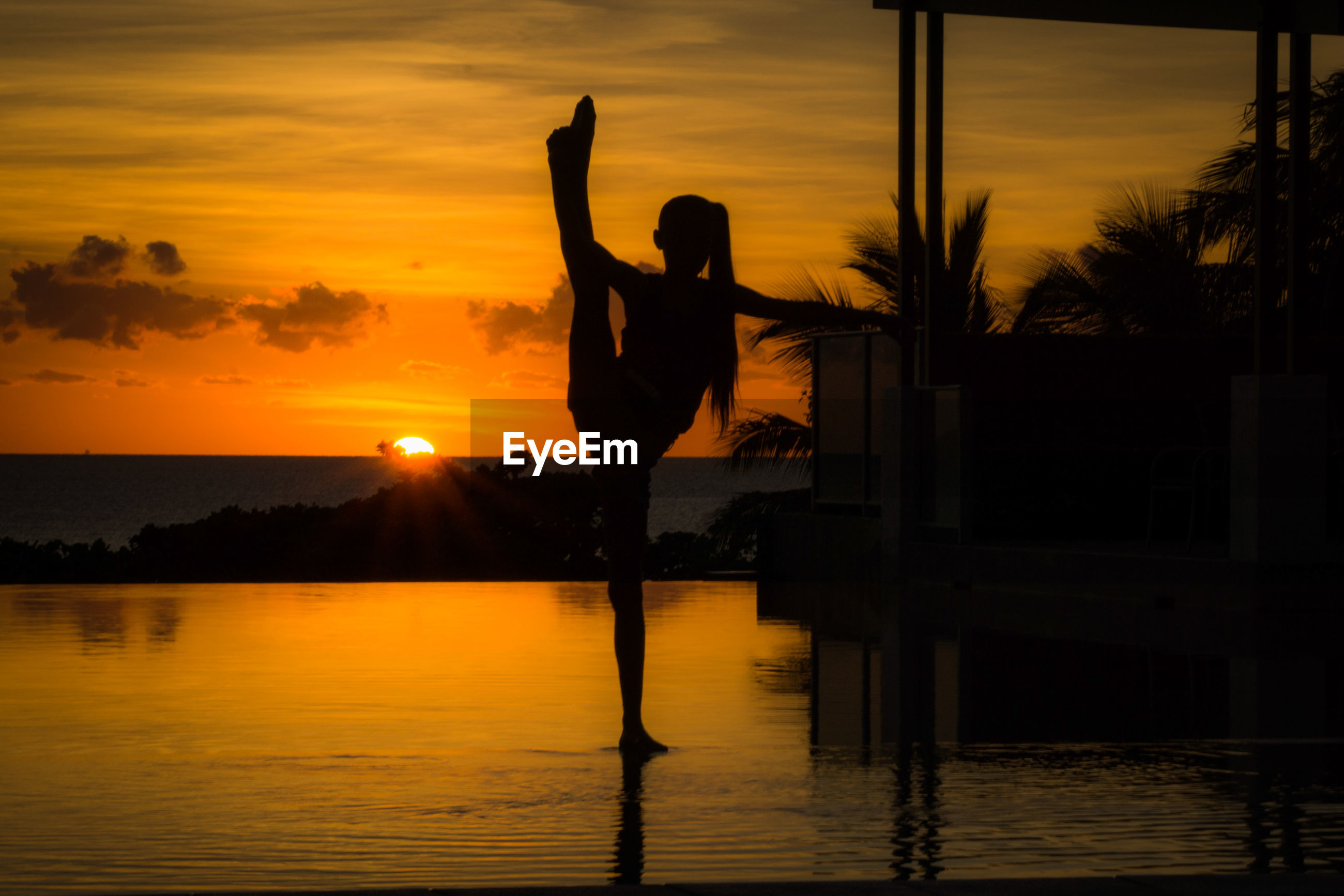 SILHOUETTE WOMAN WITH ARMS RAISED AT SUNSET