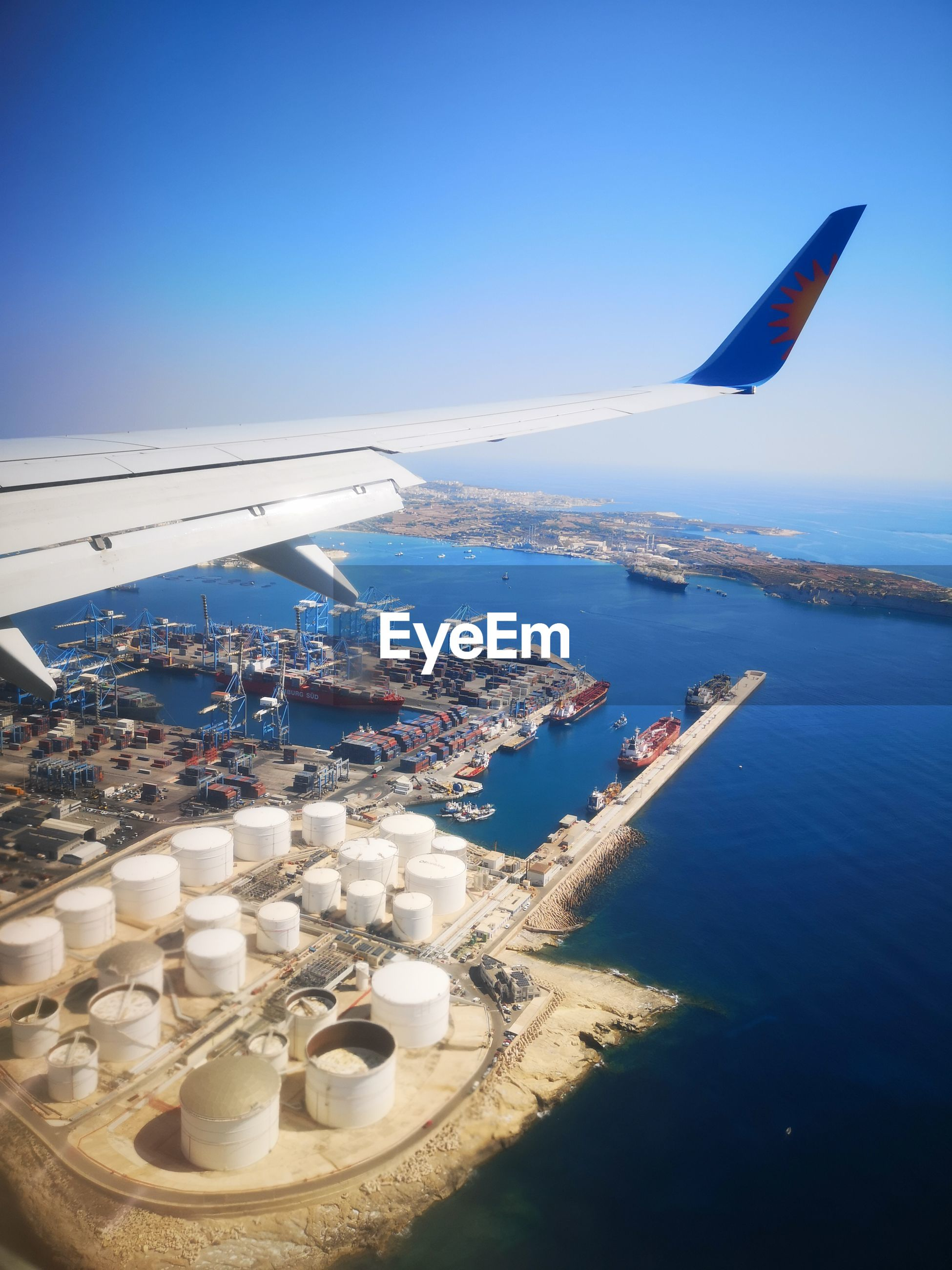 AERIAL VIEW OF SEA AND AIRPLANE FLYING ABOVE BLUE SKY