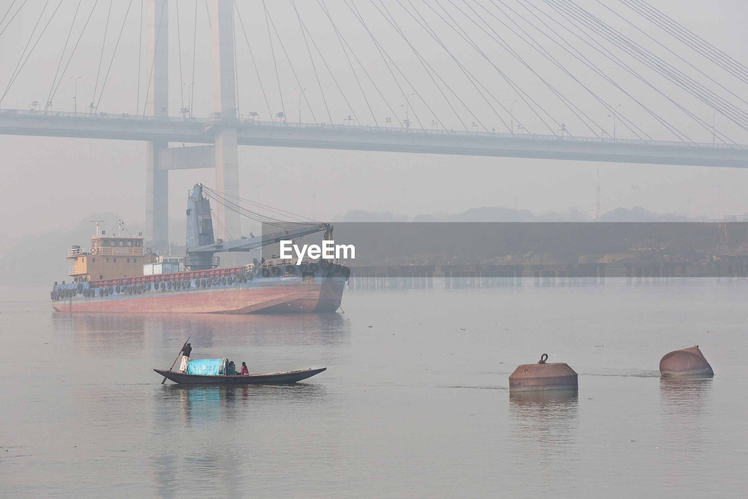Scenic view of boats in water next to bridge