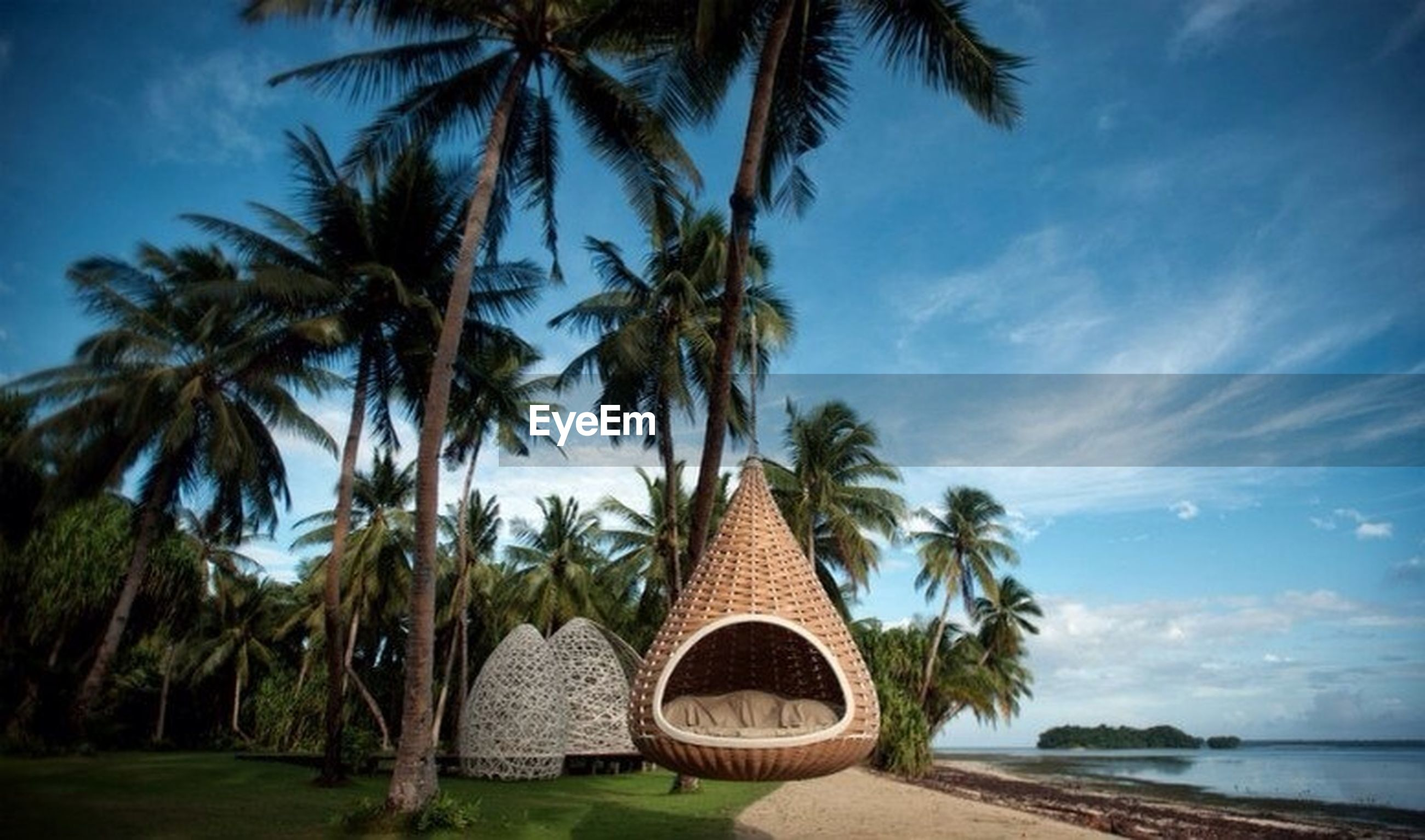 palm tree, tree, sky, growth, tranquility, nature, tranquil scene, built structure, tree trunk, cloud - sky, scenics, beach, coconut palm tree, green color, beauty in nature, outdoors, day, cloud, travel destinations, architecture
