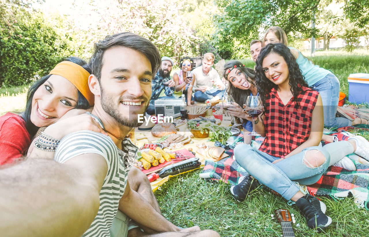happiness, smiling, young adult, young men, togetherness, young women, group of people, emotion, friendship, men, portrait, bonding, leisure activity, looking at camera, casual clothing, lifestyles, sitting, adult, picnic