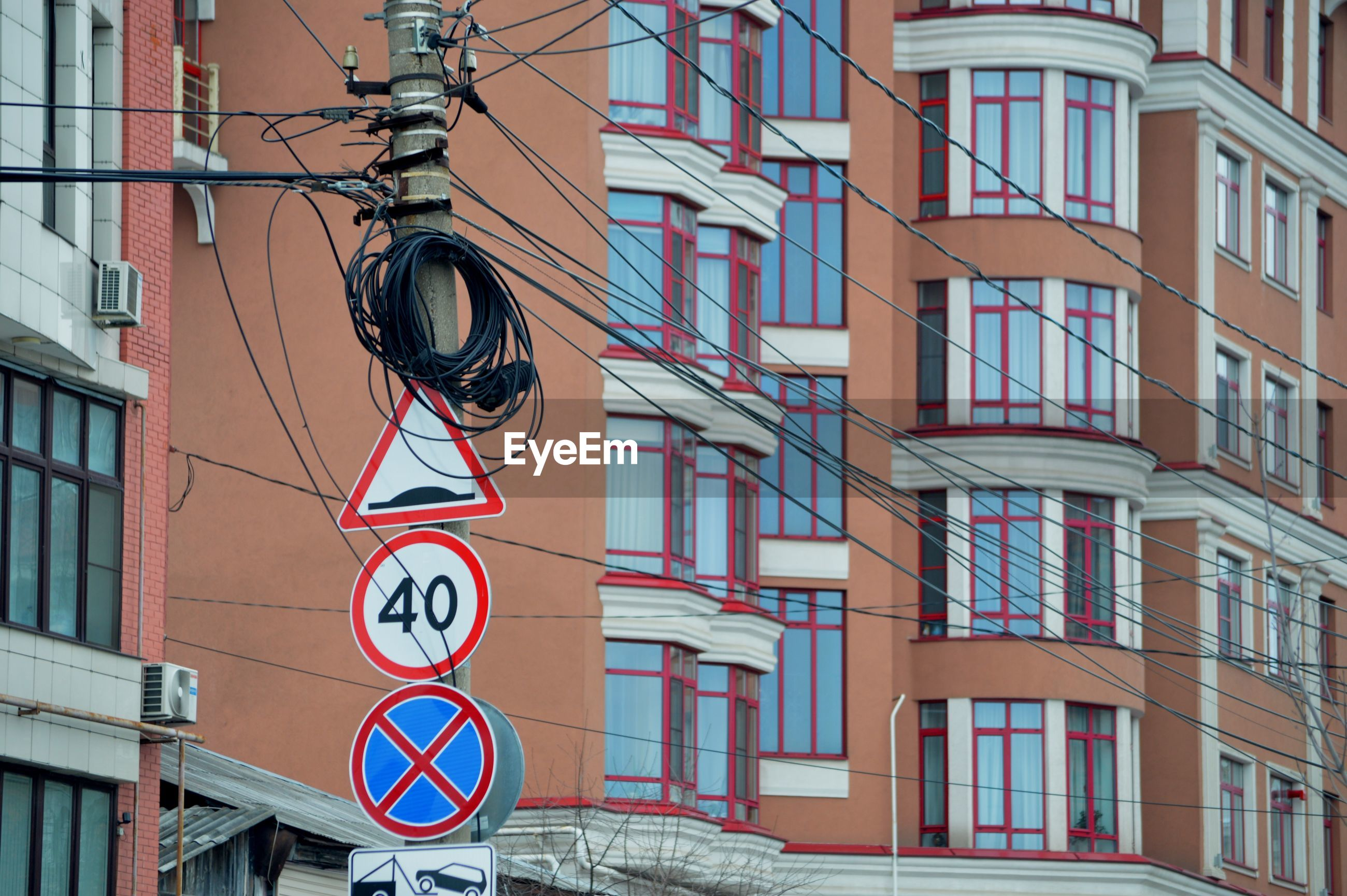 Low angle view of road sign against buildings in city