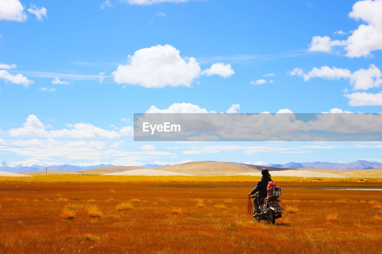 Man On Motorcycle Looking At Hilly Landscape