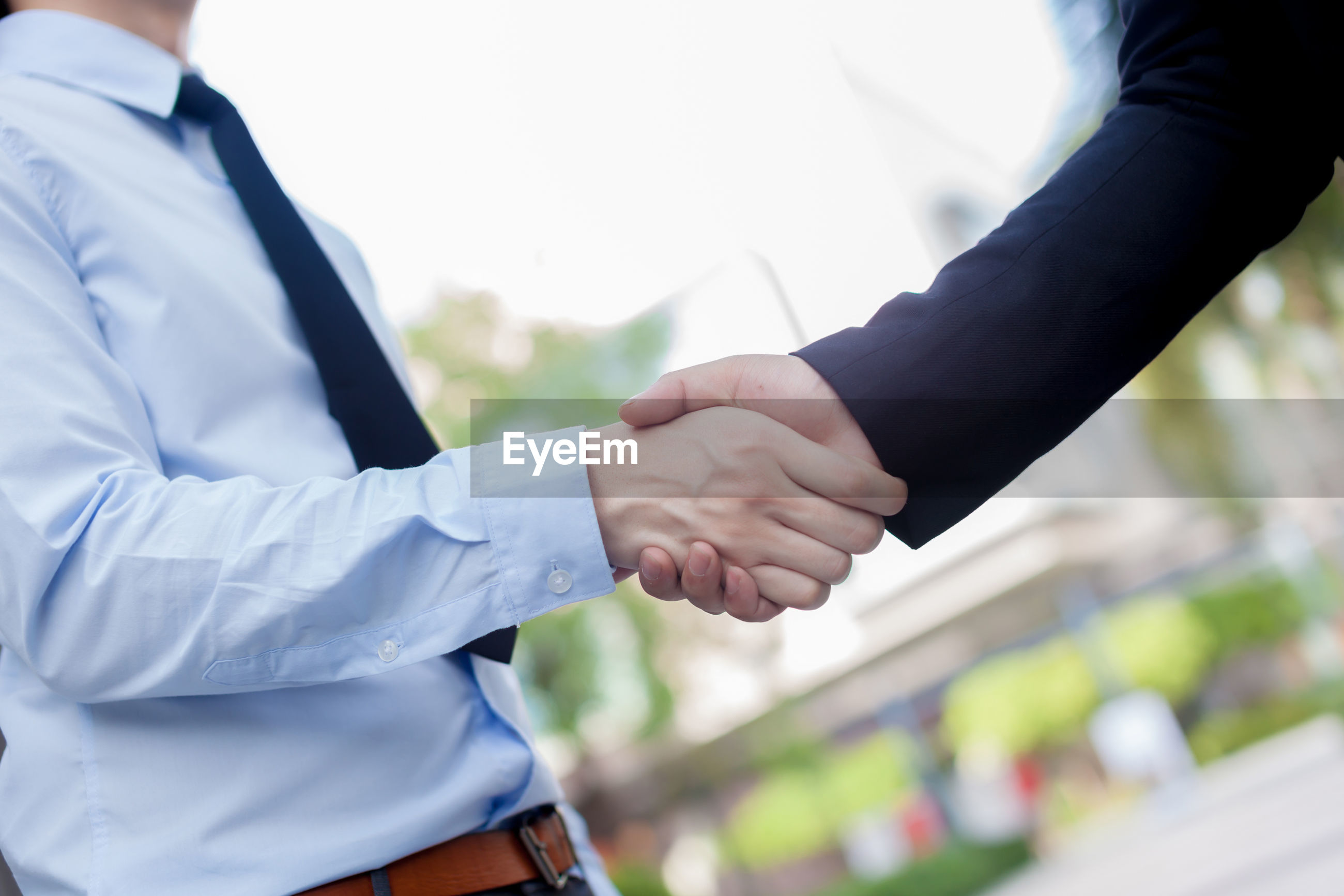 Cropped image of colleagues shaking hands in city