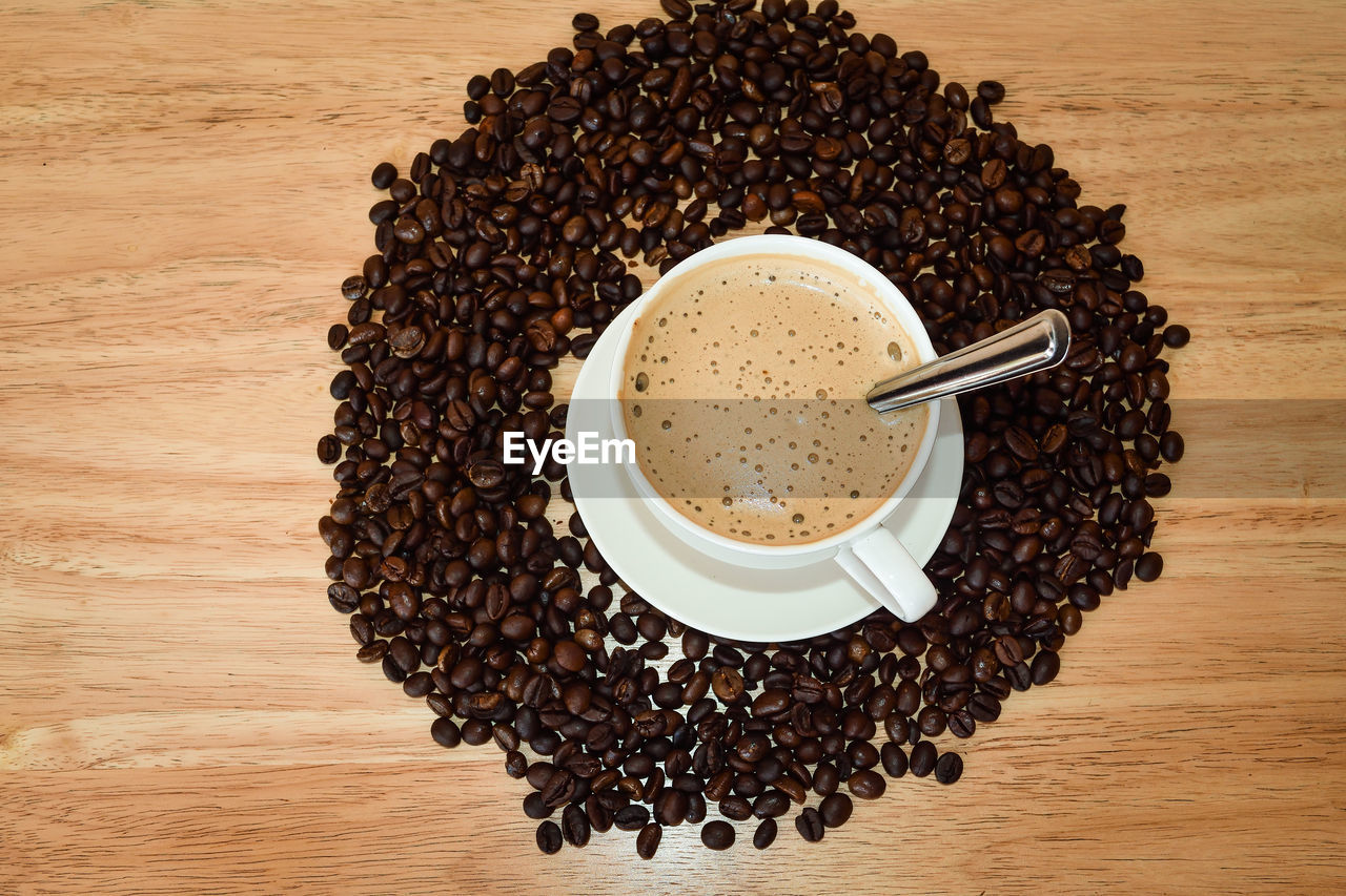 coffee - drink, coffee cup, roasted coffee bean, food and drink, drink, cup, espresso, coffee bean, table, frothy drink, refreshment, roasted, still life, cappuccino, freshness, brown, morning, no people, high angle view, latte, breakfast, indoors, studio shot, ground coffee, directly above, preparation, close-up, raw coffee bean, mocha, froth art, coffee break, day