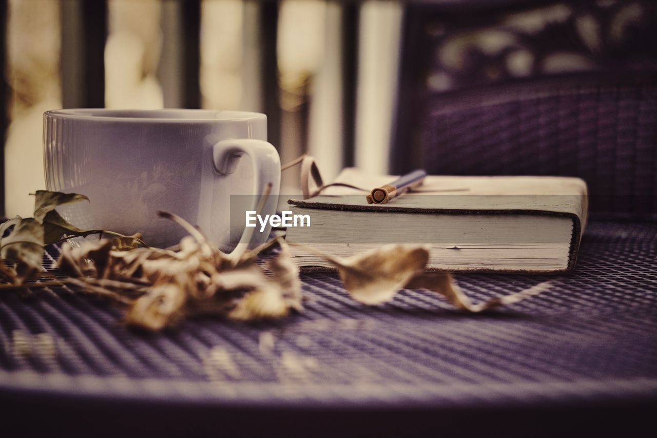 Coffee With Dried Leaves And Book On Table