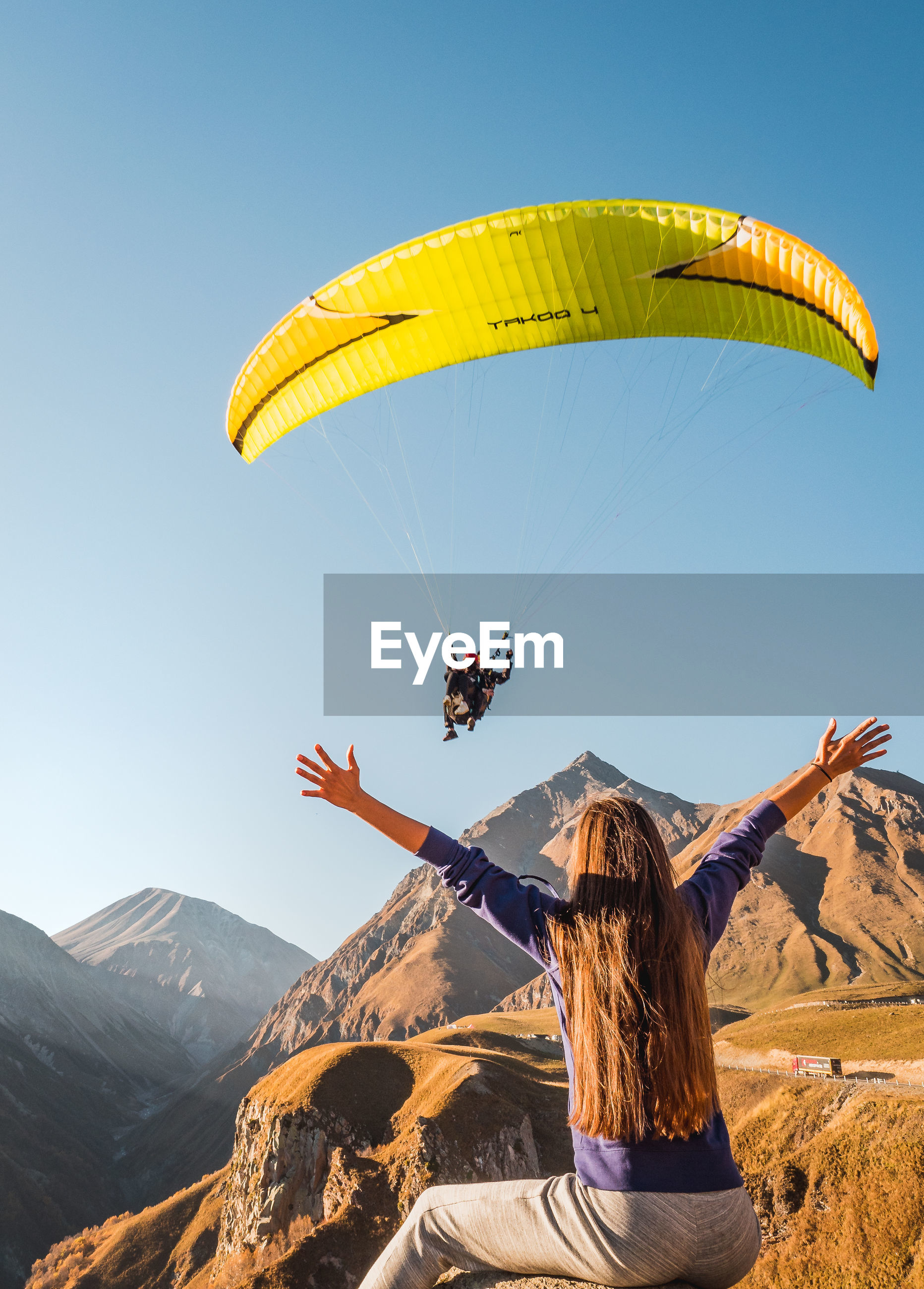 REAR VIEW OF PERSON PARAGLIDING AGAINST MOUNTAINS