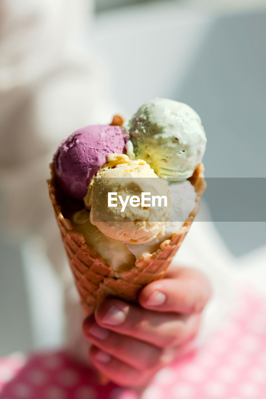 CLOSE-UP OF HAND HOLDING ICE CREAM CONE ON GLASS