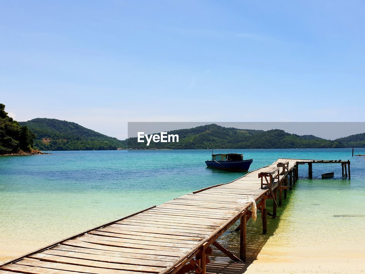 water, tranquility, scenics, tranquil scene, nature, beauty in nature, sea, mountain, outdoors, day, pier, clear sky, no people, wood - material, jetty, blue, sky, nautical vessel, tree