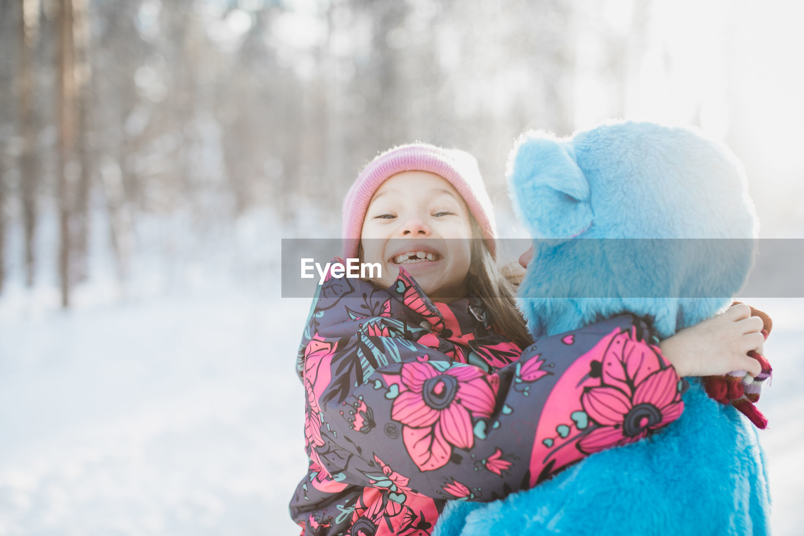 Close-up portrait of smiling girl with father on snow