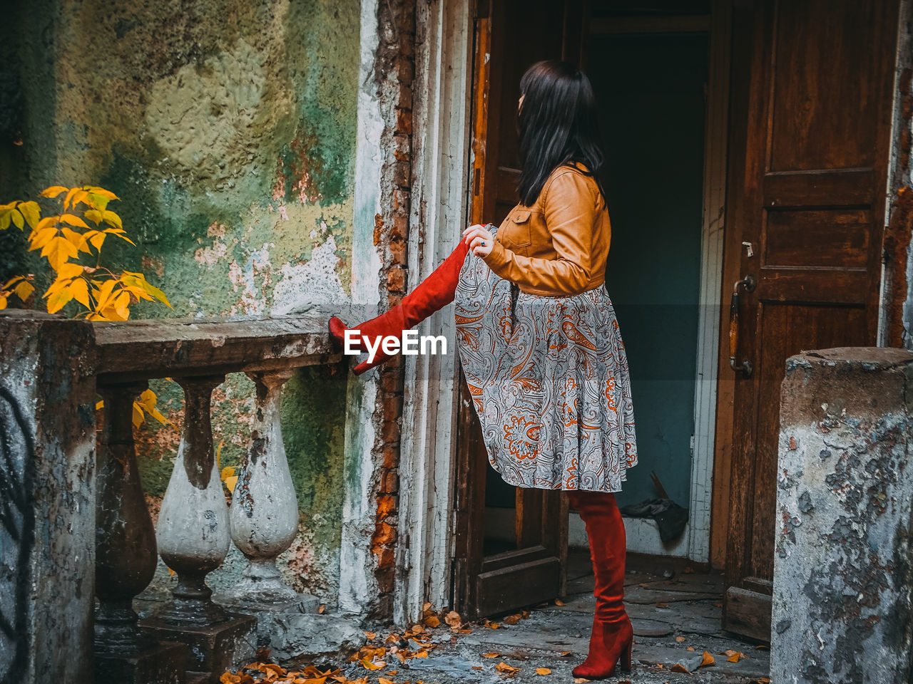 Full Length Of Woman Standing Outside Abandoned House