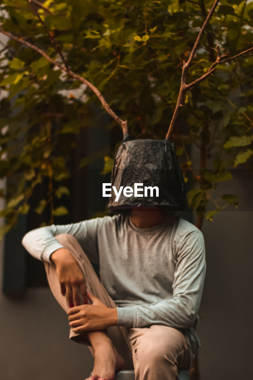 one person, real people, three quarter length, casual clothing, clothing, leisure activity, front view, lifestyles, men, adult, holding, tree, obscured face, hat, standing, plant, nature, focus on foreground, sitting