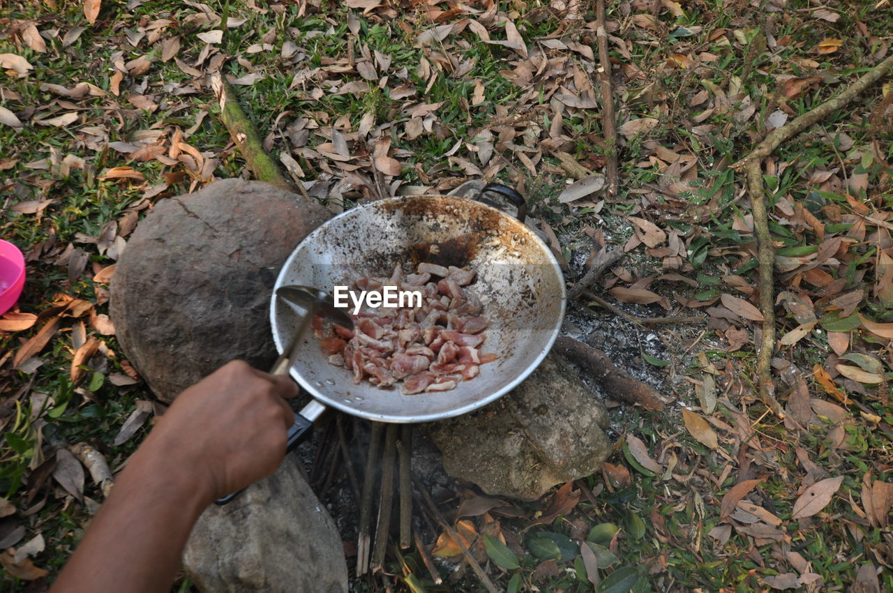 Man Cooking Meat In Frying Pan On Campfire In Forest