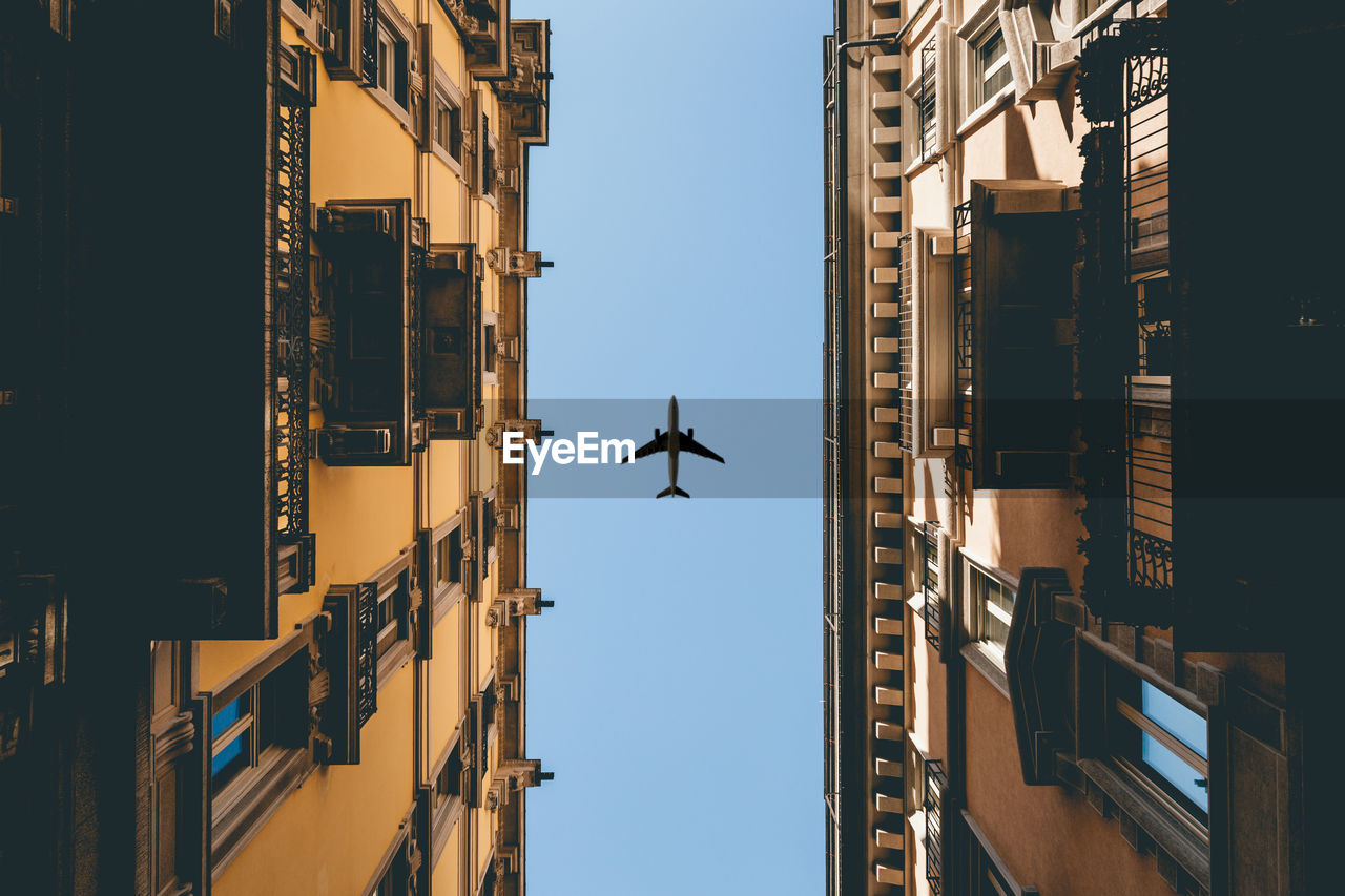flying, architecture, building exterior, built structure, air vehicle, mid-air, low angle view, transportation, airplane, mode of transportation, building, sky, city, no people, day, residential district, motion, clear sky, travel, on the move, outdoors, office building exterior, flight, directly below, skyscraper, apartment, aerospace industry