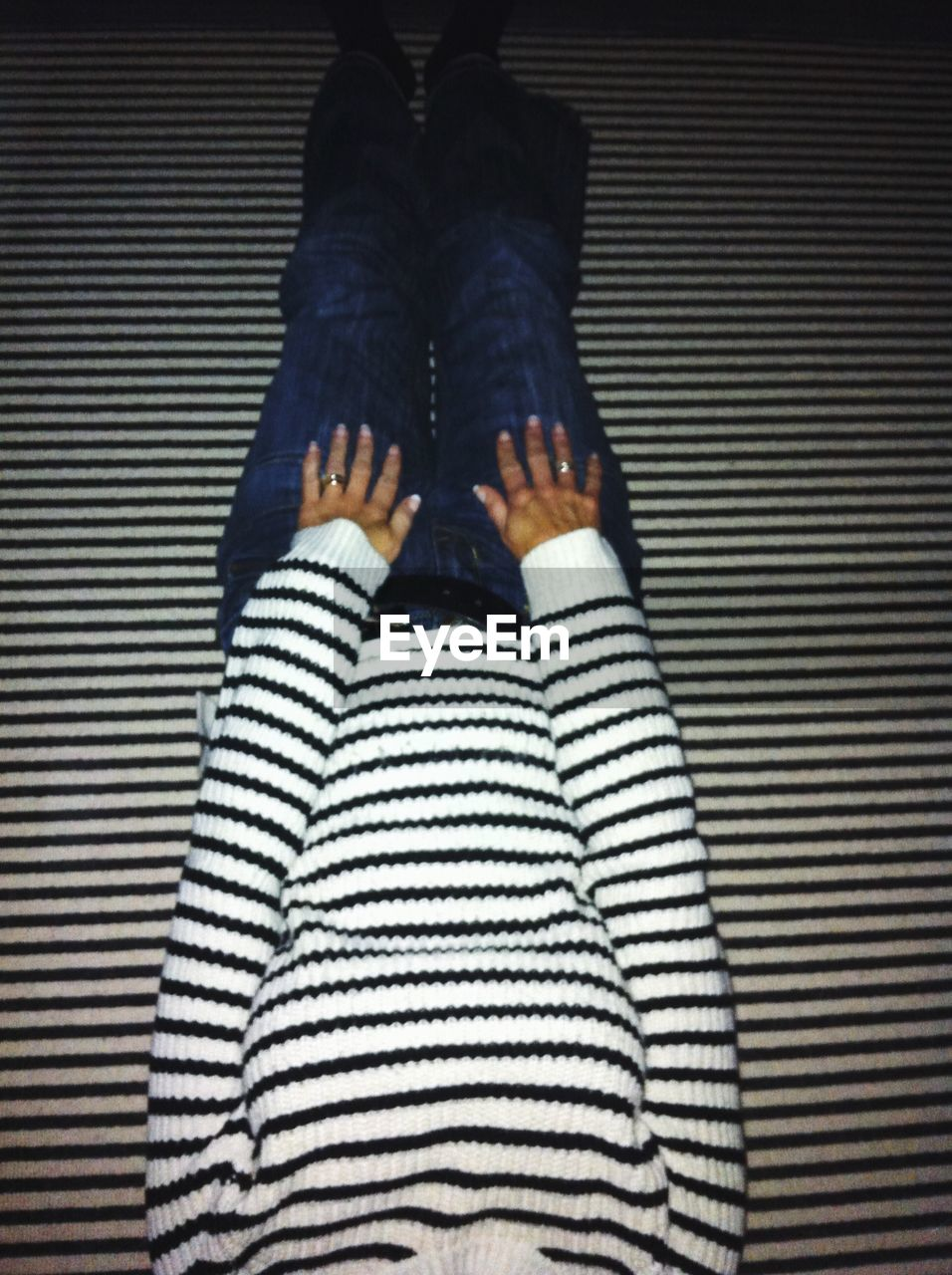 Midsection of woman relaxing on striped floor