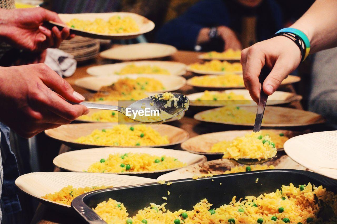 Close-Up Of Hands Serving Food