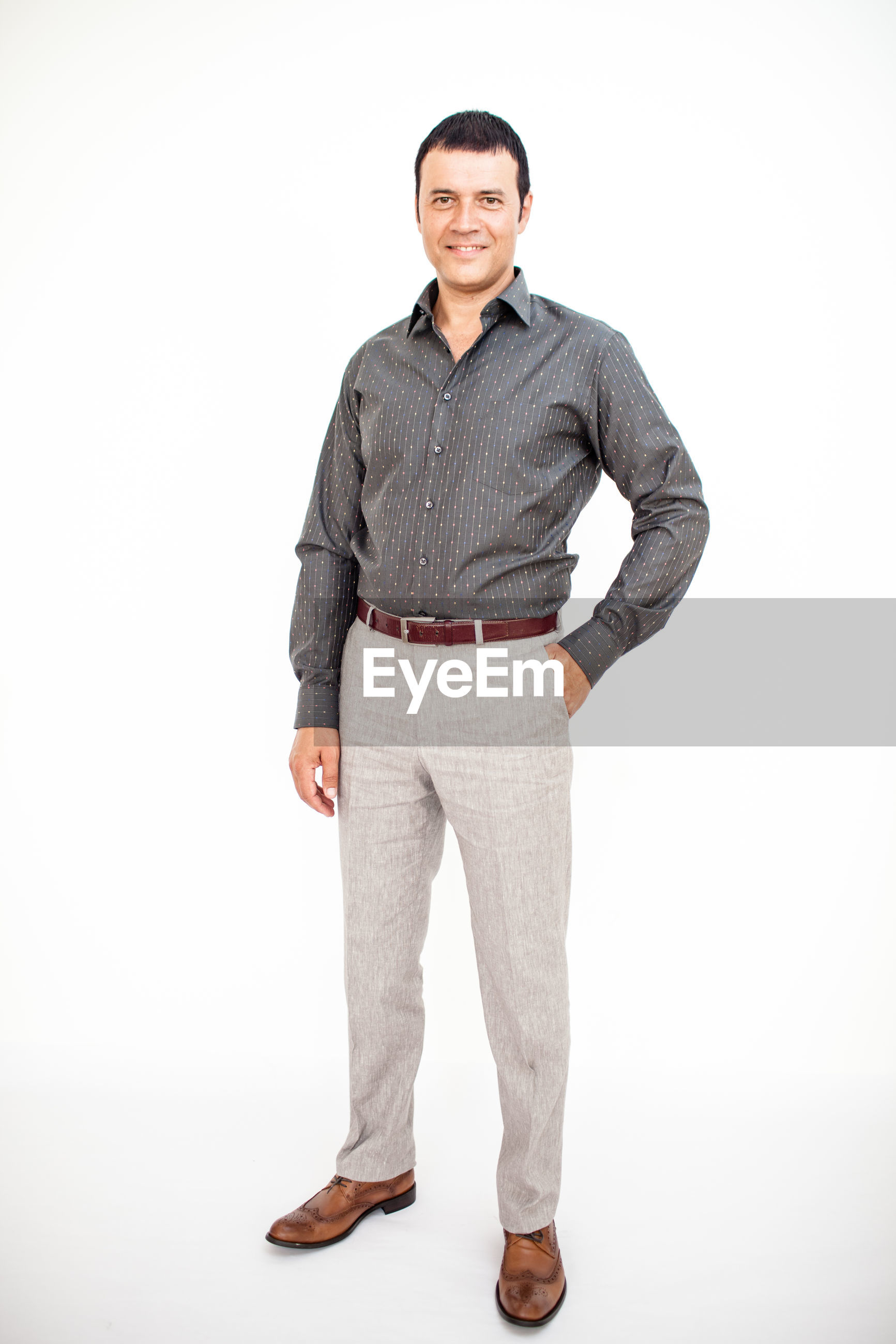 Portrait of mature man standing against white background