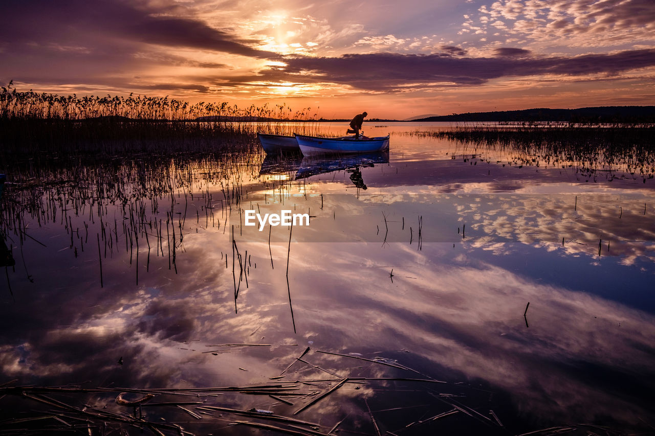 water, nautical vessel, transportation, sky, sunset, mode of transportation, cloud - sky, reflection, beauty in nature, scenics - nature, nature, tranquility, tranquil scene, orange color, idyllic, lake, moored, non-urban scene, no people, outdoors