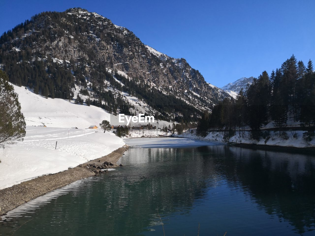 water, mountain, scenics - nature, beauty in nature, sky, tranquility, tranquil scene, cold temperature, winter, lake, snow, tree, nature, mountain range, day, reflection, waterfront, no people, outdoors, snowcapped mountain, mountain peak