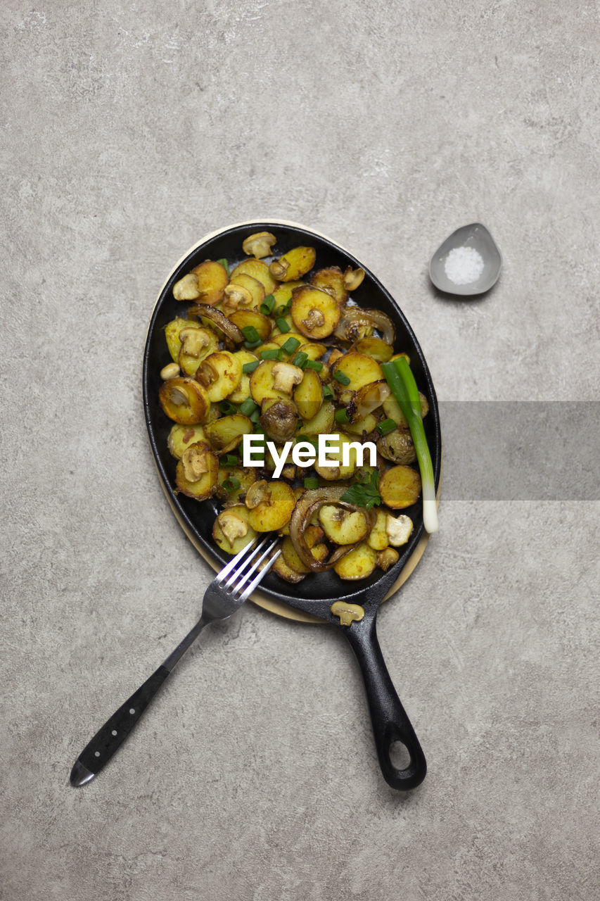 kitchen utensil, directly above, healthy eating, food, food and drink, wellbeing, freshness, studio shot, eating utensil, indoors, spoon, vegetable, household equipment, no people, cooking pan, high angle view, gray background, close-up, pan, still life, frying pan, vegetarian food, skillet- cooking pan, garnish