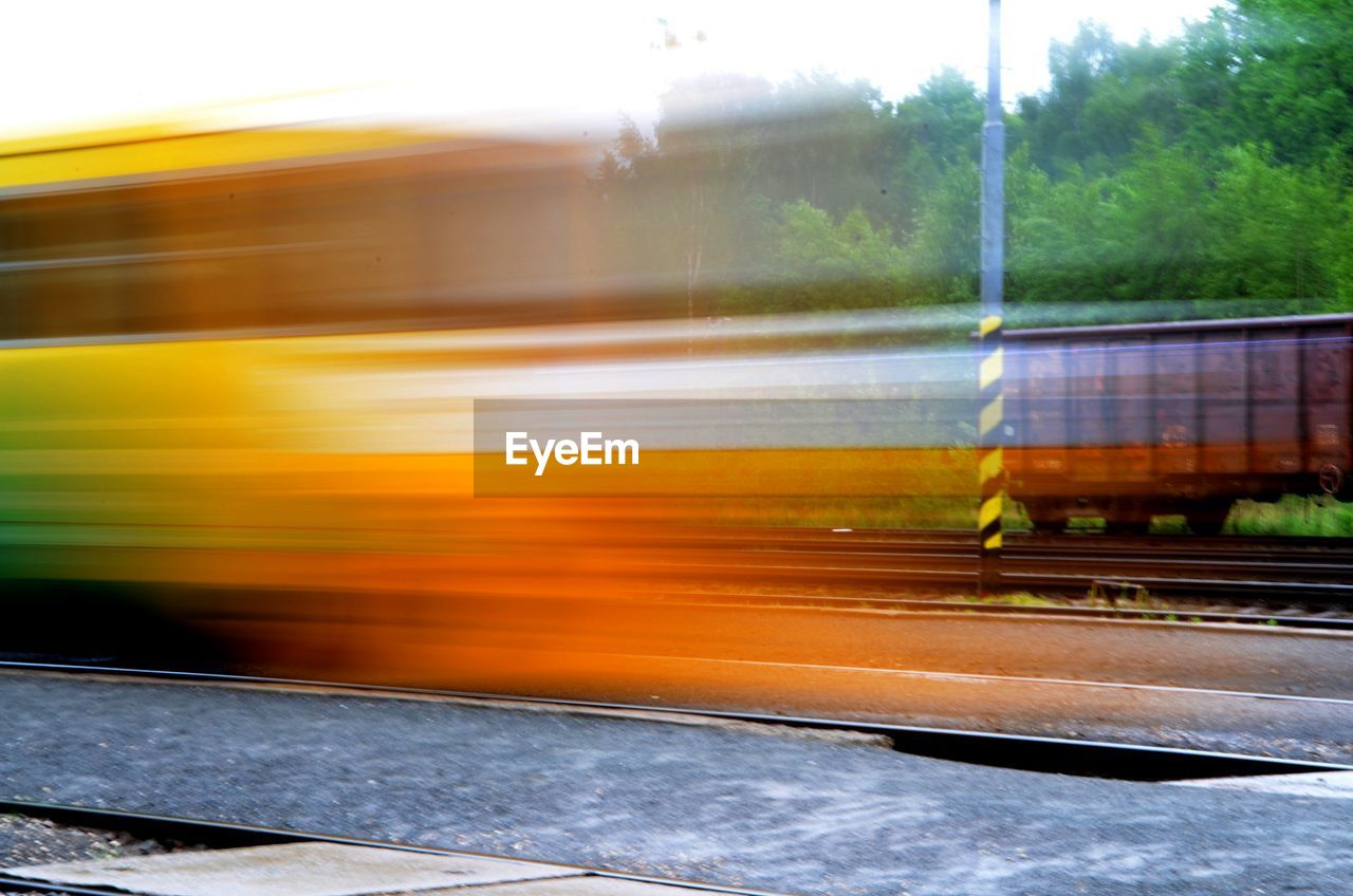 transportation, mode of transport, blurred motion, train - vehicle, public transportation, speed, rail transportation, motion, yellow, land vehicle, no people, day, railroad station platform, outdoors, sky