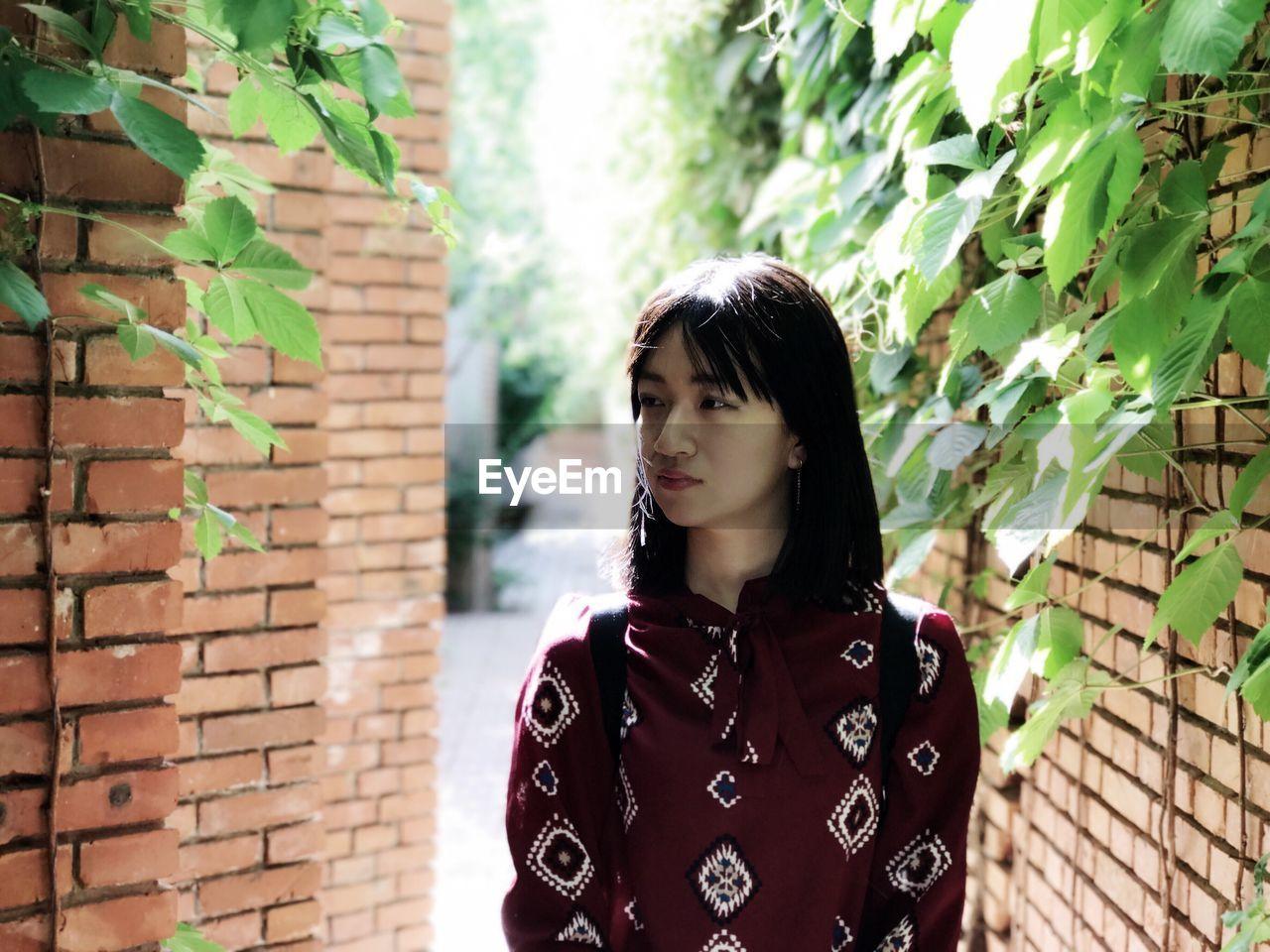 Young woman walking brick walls