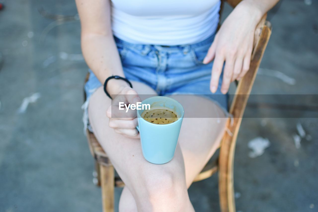 Midsection of woman with coffee cup
