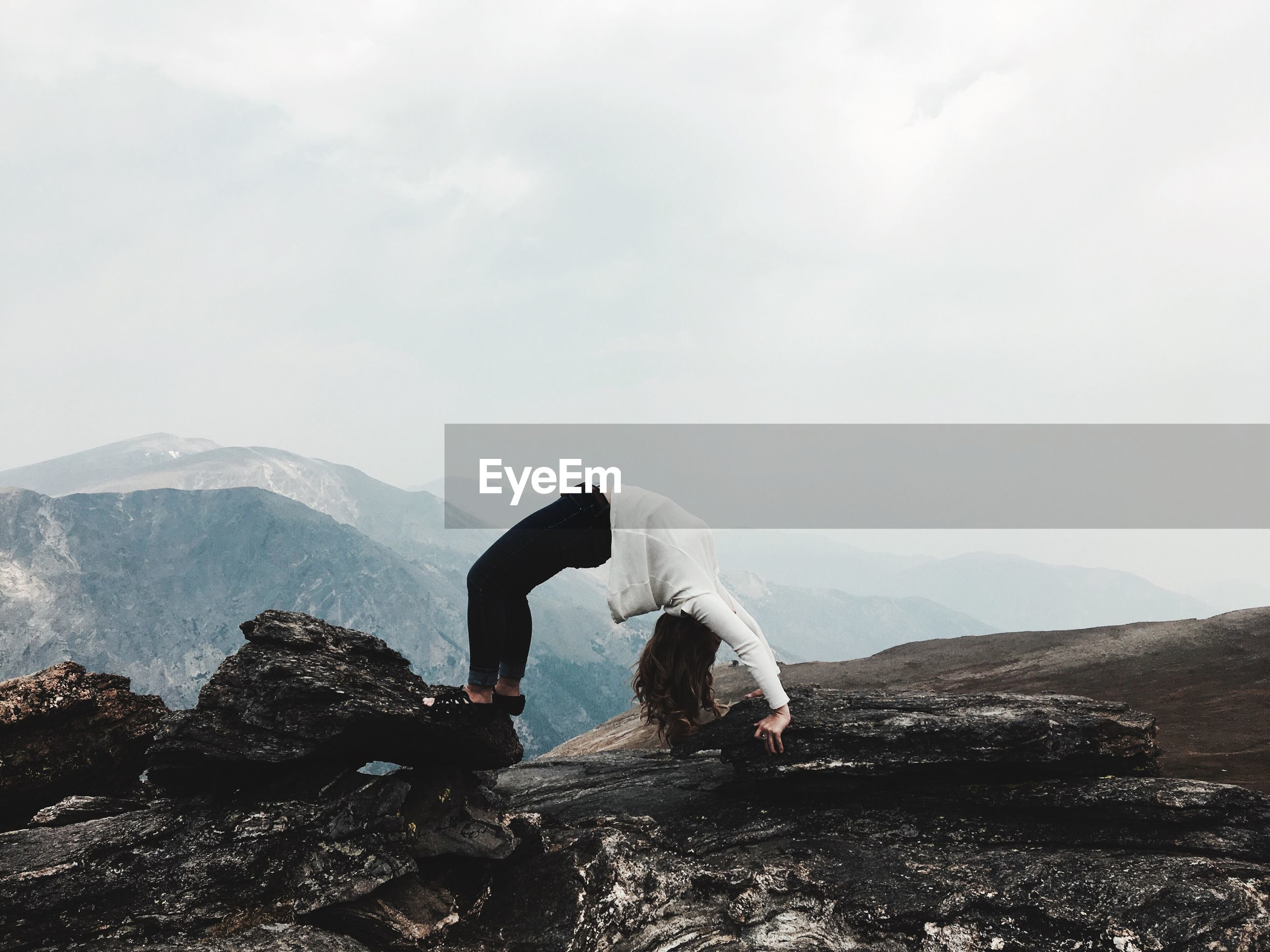 Woman standing on mountain against sky