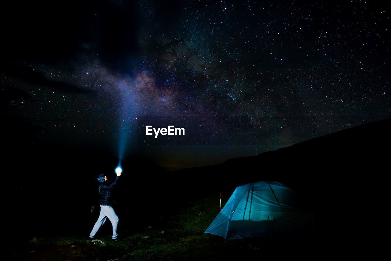 Side View Of Man With Illuminated Flashlight Against Star Field At Night